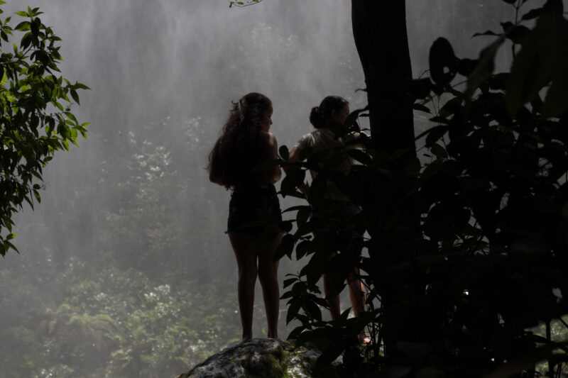 Young women by a waterfall in a tropical forest