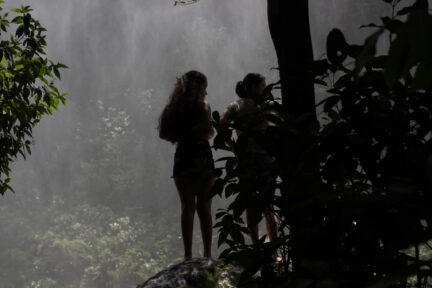 Youg women by waterfall in tropical forest