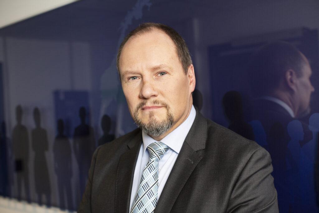 Direktør i SKM Gudmund Gjølstad stående foran blått skilt