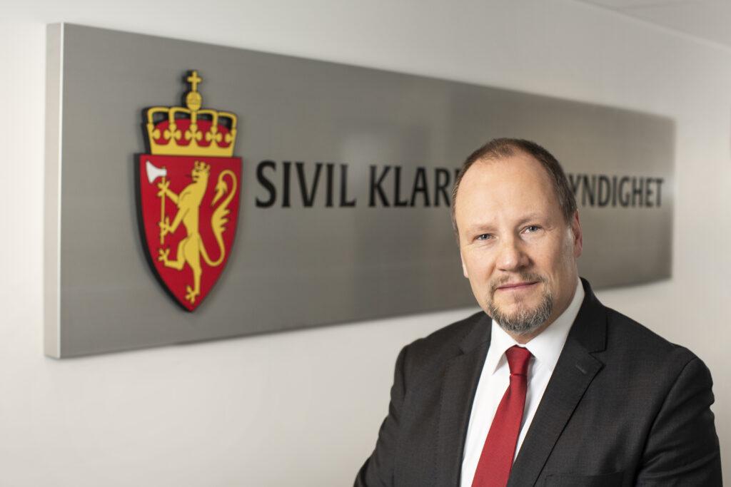 Direktør i SKM Gudmund Gjølstad foran SKM skilt