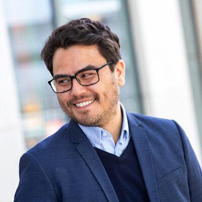 Bilde av Lars Erik Mangset i blå dress og mørk genser som smiler og ser ned til høyre