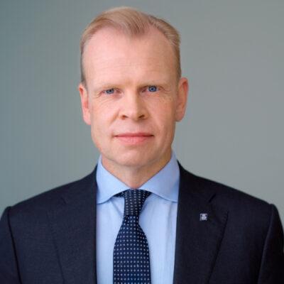 Bilde av Svein Tore Holsether, i mørk dress med blå skjorte som ser mot kameraet